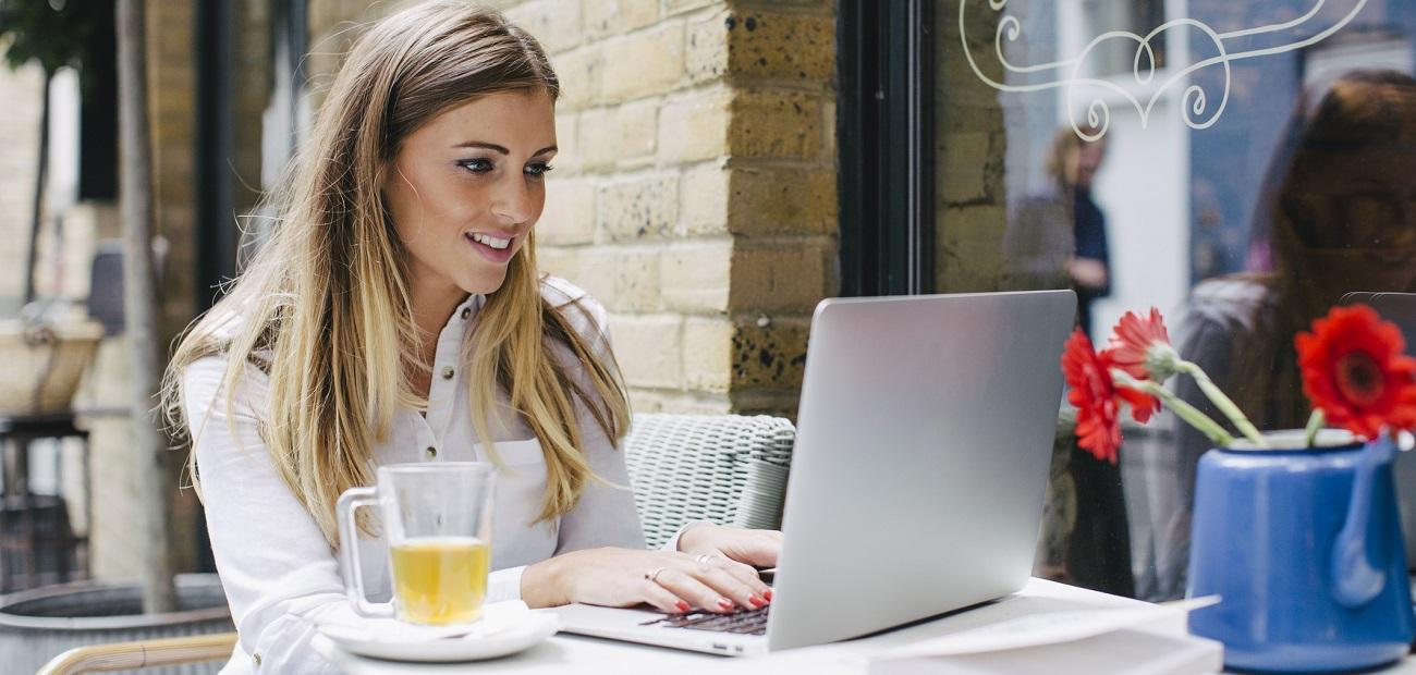 blogger typing on laptop in a coffee shop