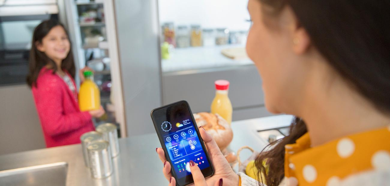 Mother using smart phone app to track groceries in refrigerator