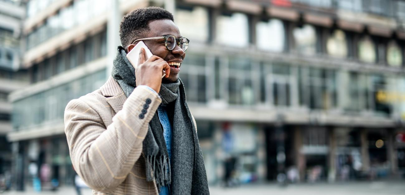African American businessperson walking through city talking on the phone