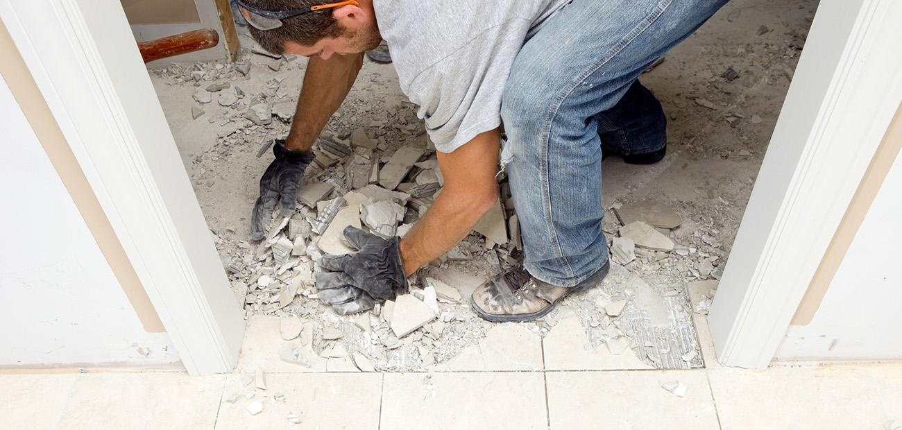 Construction worker picking up marble tile which has been demolished between an interior doorway for house remodeling project