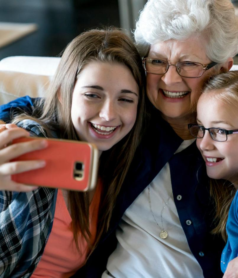 happy grandmother and granddaughters taking selfie