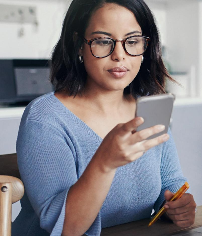 woman sitting at kitchen table, checking her phone