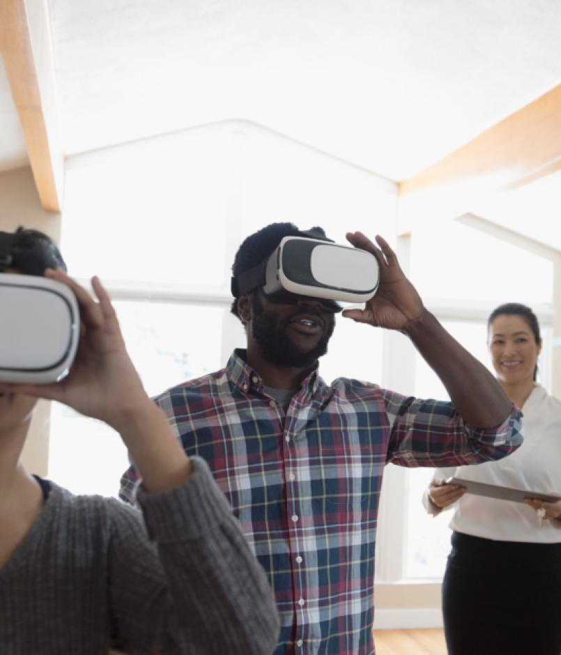 Agent showing young couple new house, using virtual reality goggles