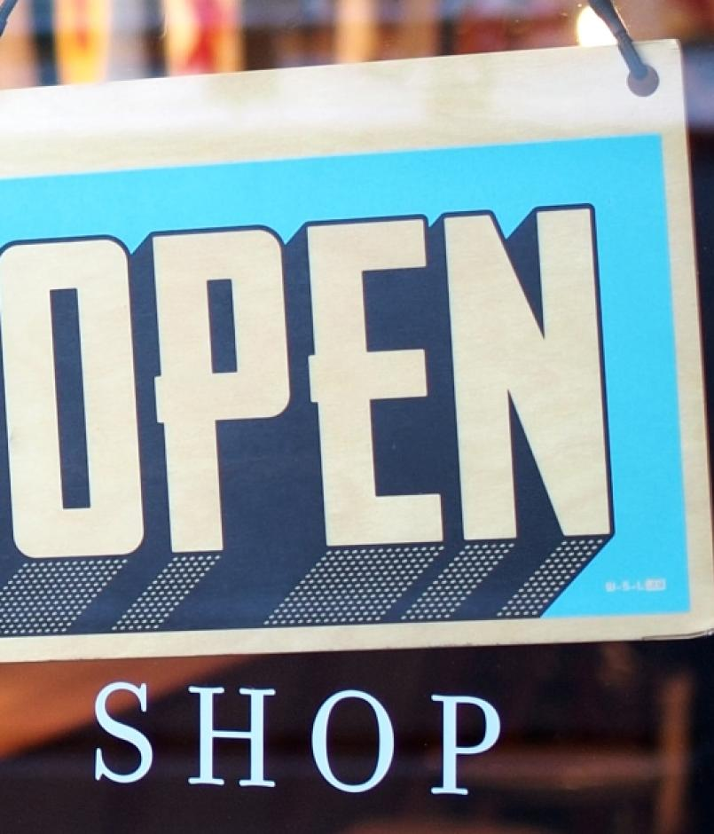 "An ""Open"" sign on a storefront door"