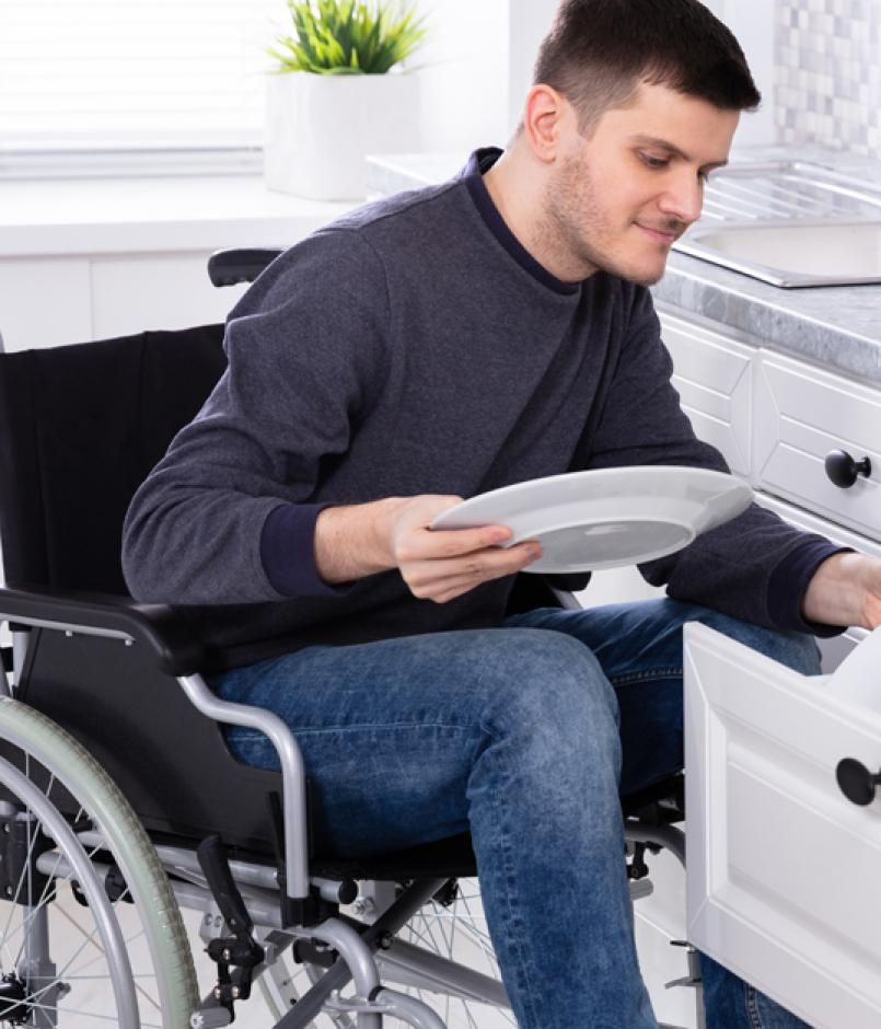 Disabled Man in Wheelchair Arranging Plates