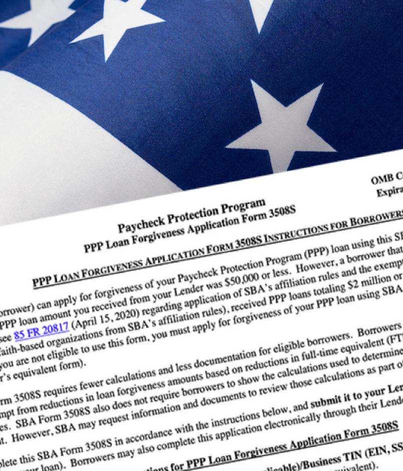 PPP Forgiveness application on a background of US flag and money