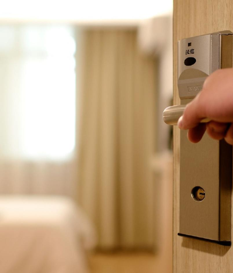 View of someone's hand and arm opening the door to a hotel room