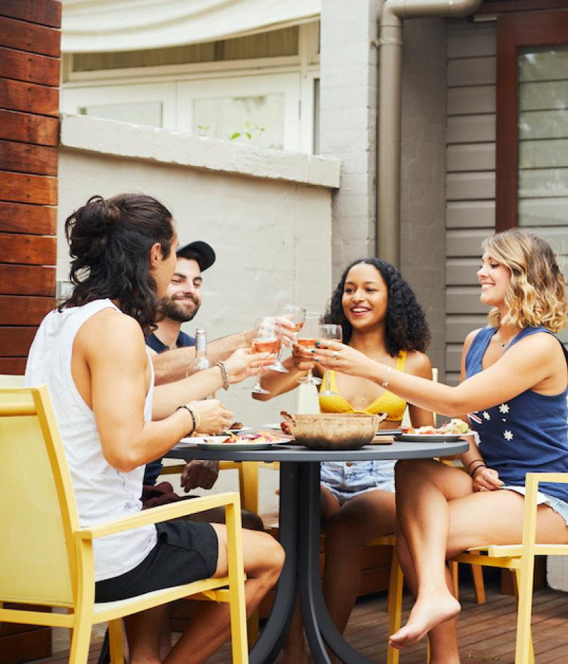 Young adults sitting round backyard table.