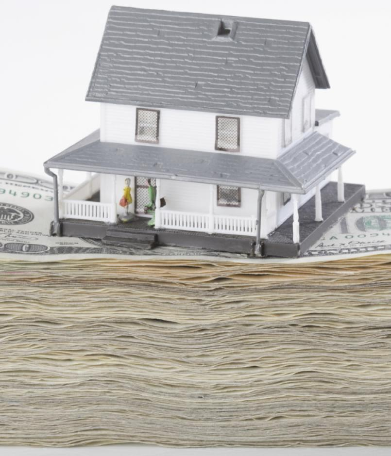 House perched on stack of $100 bills