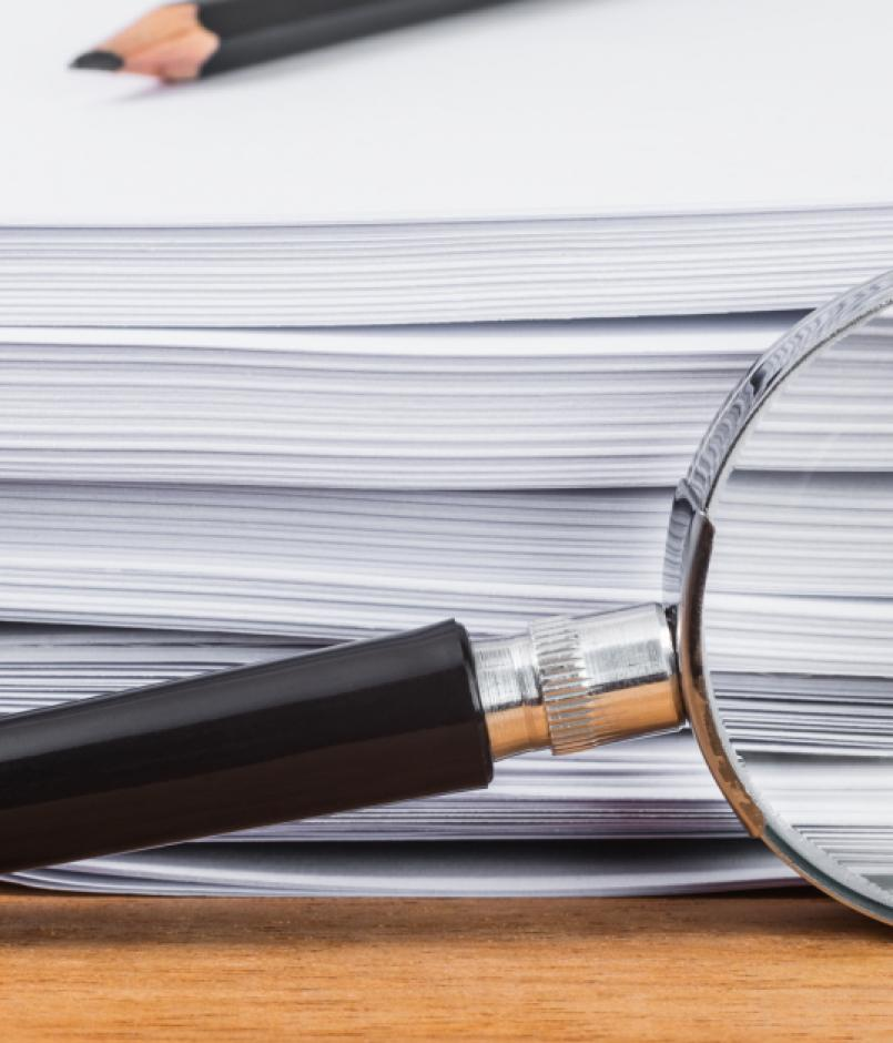 magnifying glass in front of stack of papers