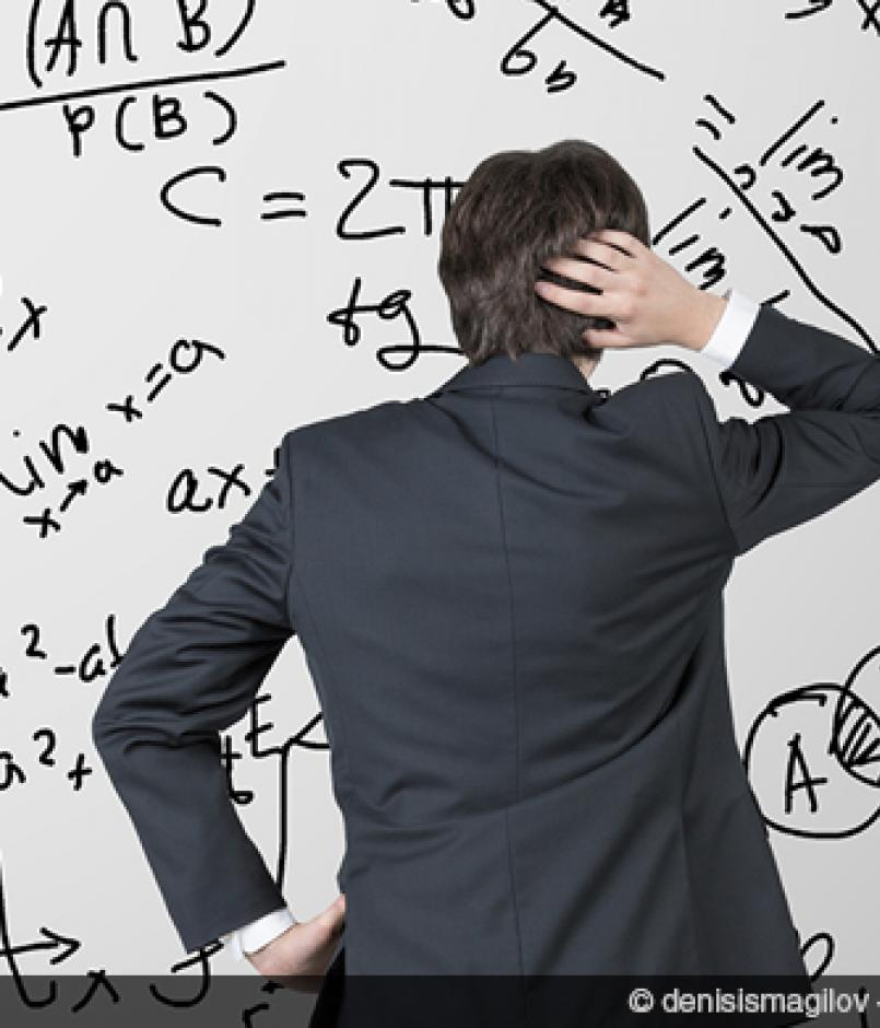 confused businessman looking at equations