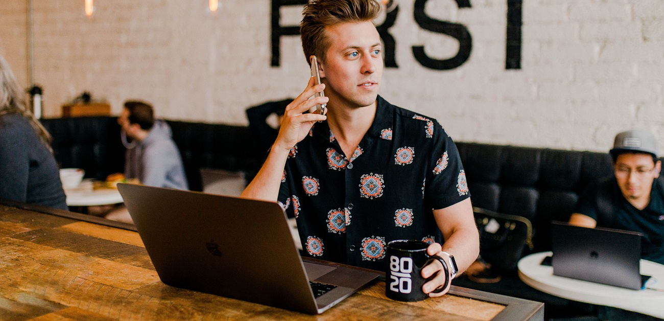 Man with laptop and phone at coffee shop