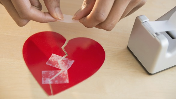 Person taping together an image of a broken heart