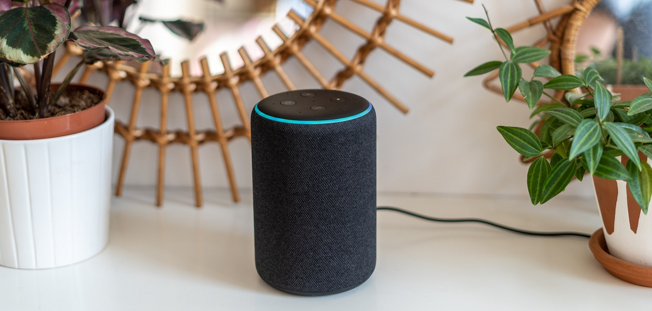 Amazon Alexa Echo Plus on a white table with green plants in the background