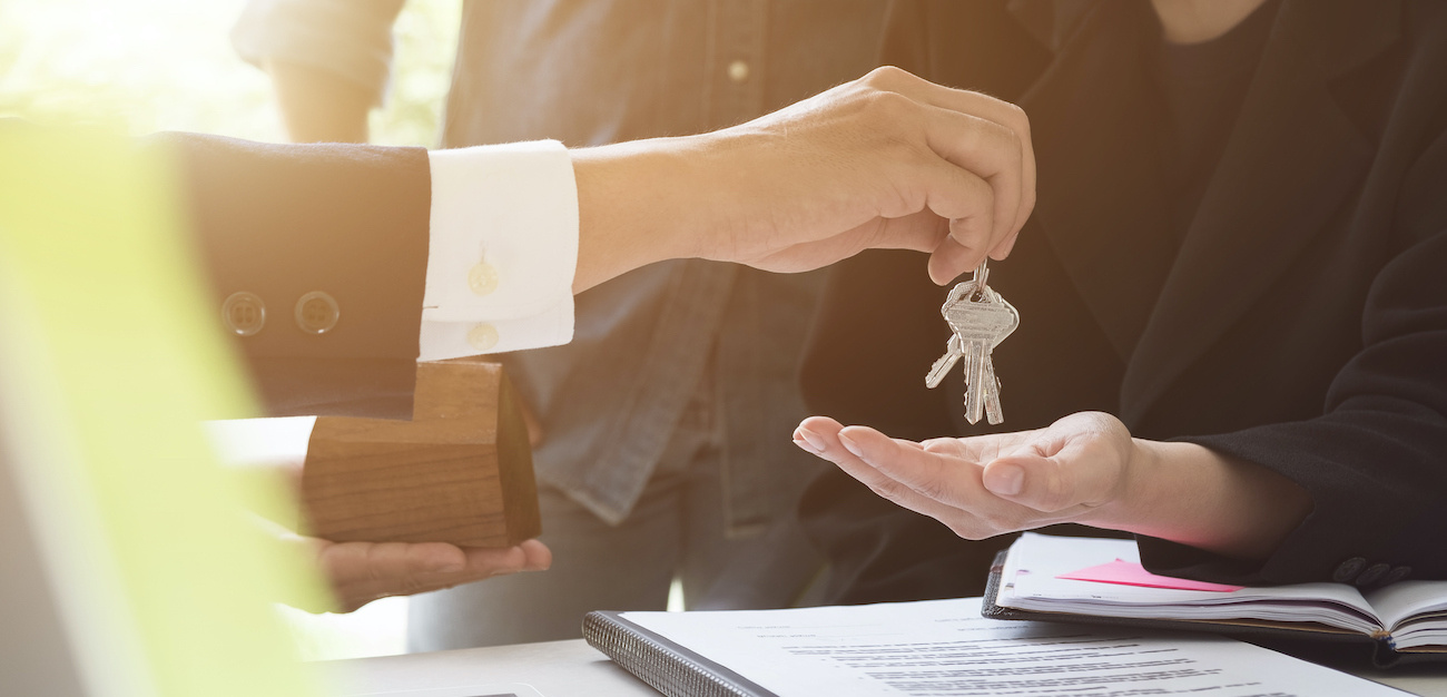 Handing keys to clients after signing paperwork.