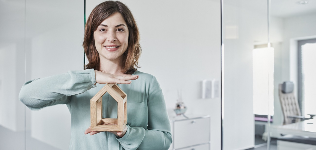 Portrait of smiling young businesswoman holding architectural model in office