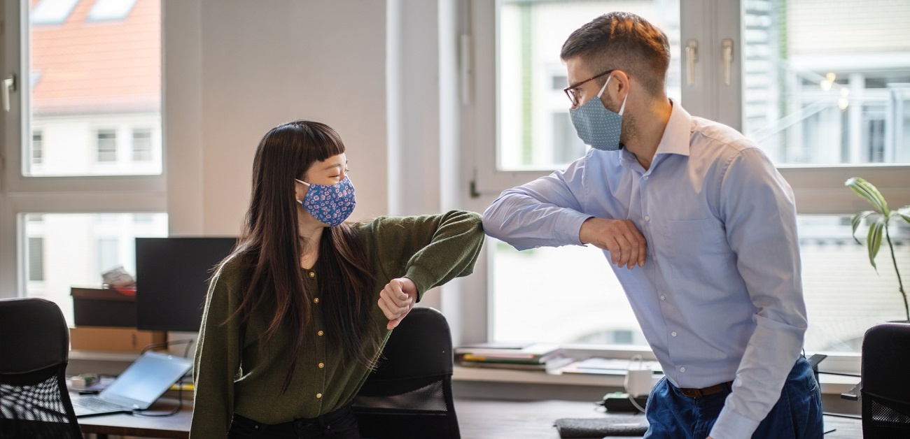 Business people greeting with elbow bump in office