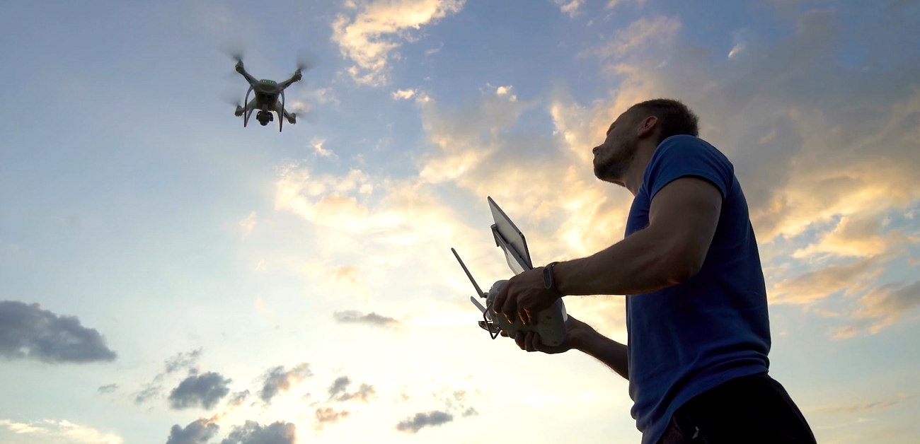 Man flying a drone at dusk