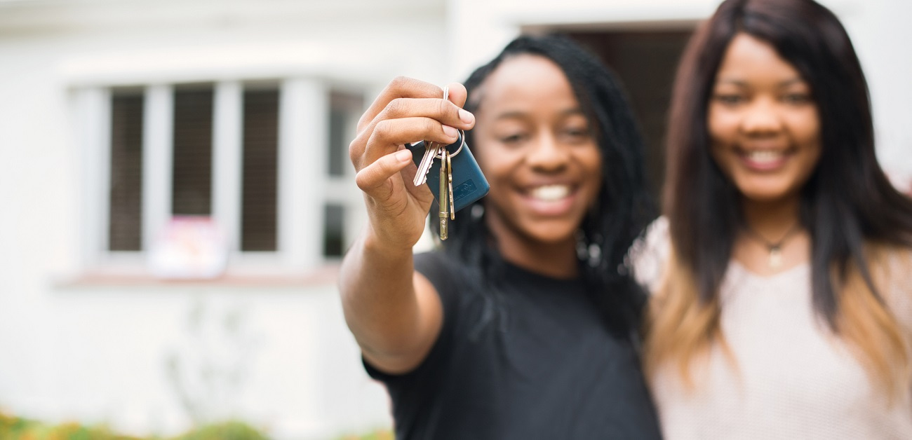 young women showing the keys of the new house