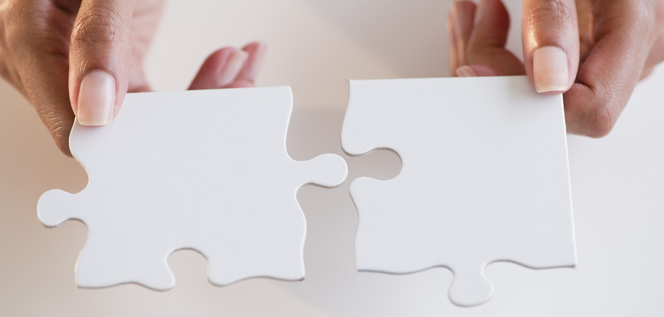 Two hands fitting puzzle pieces together