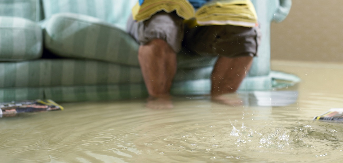 Man sitting on couch in flooded home