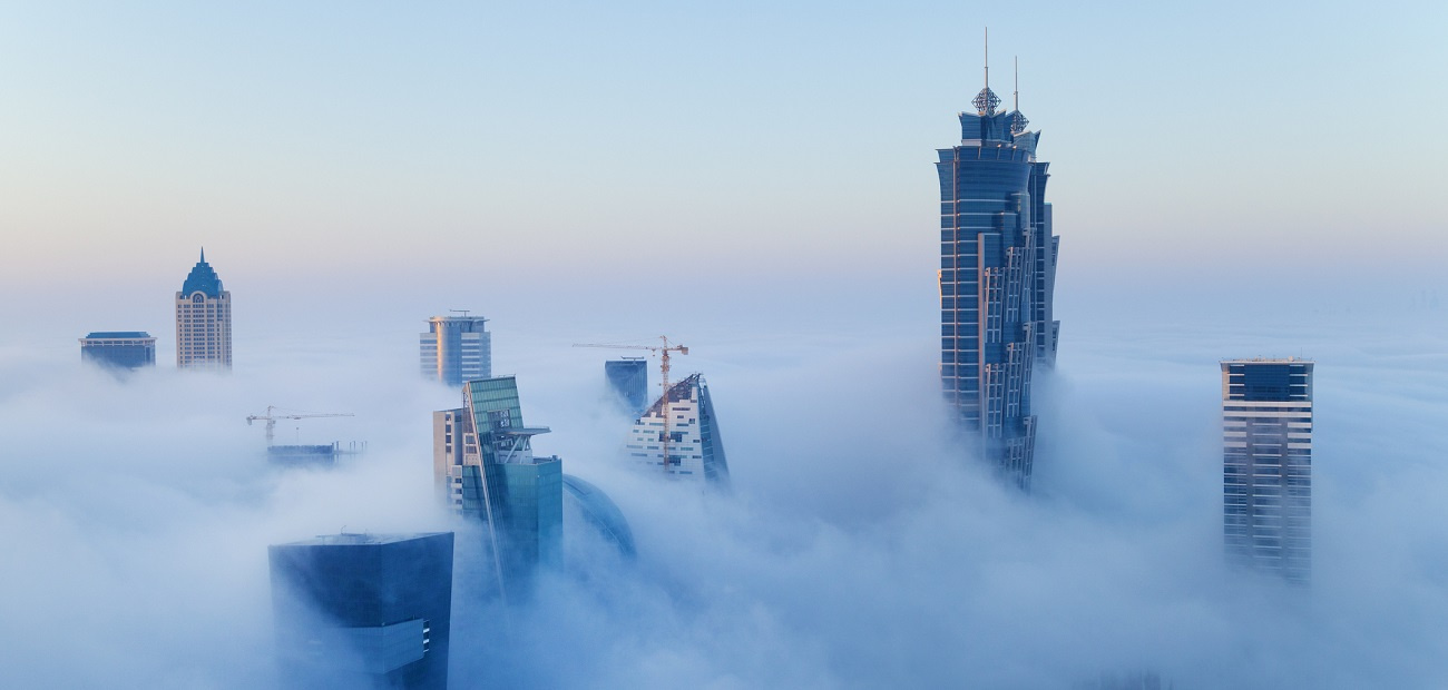 Buildings rise above clouds