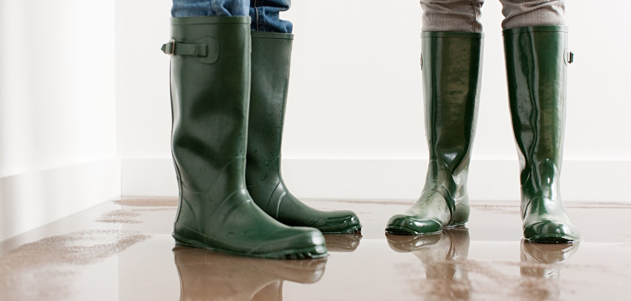 People in rainboots in a flooded home
