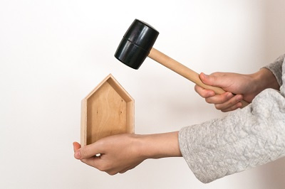 Woman hitting a wooden house with a hammer