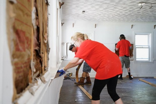 KW Cares teams remove sheetrock in a damaged home in North Carolina.