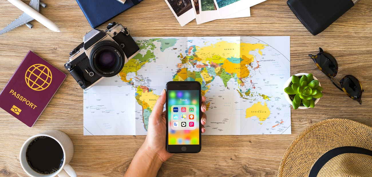 Holding a smart phone on a wooden desk with travel accessories