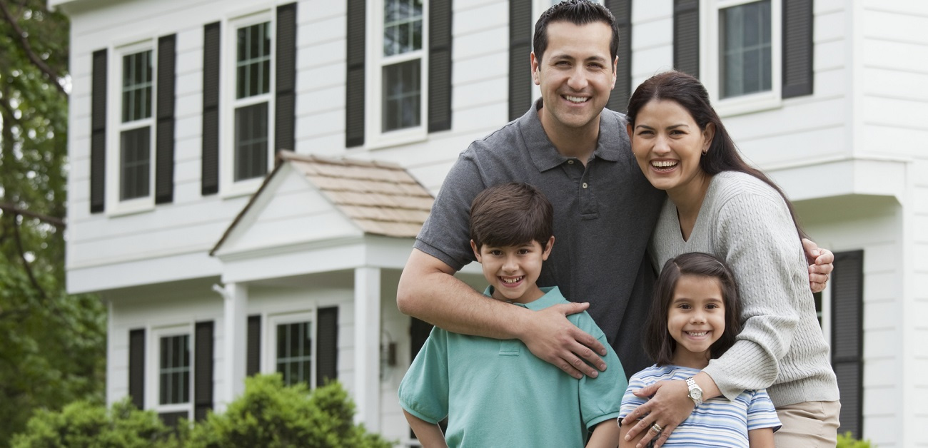 Hispanic family posing in front of house