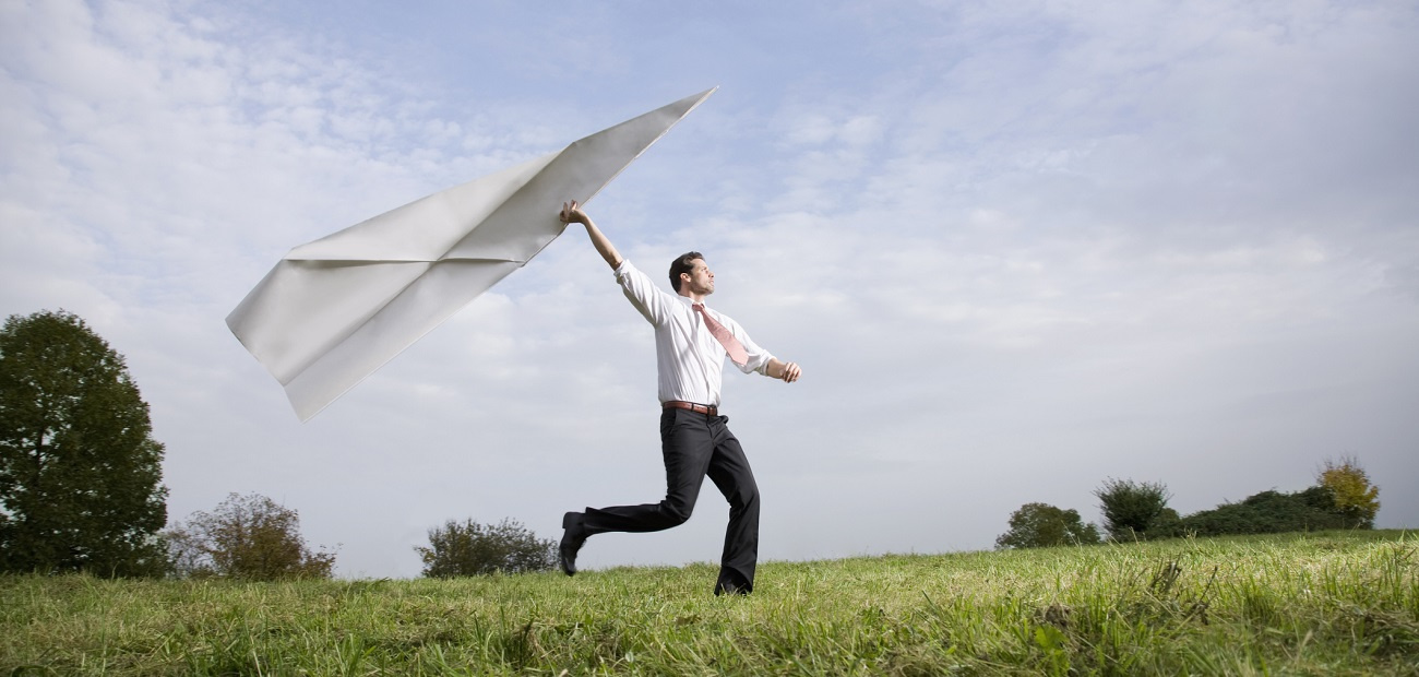 Businessman with giant paper airplane