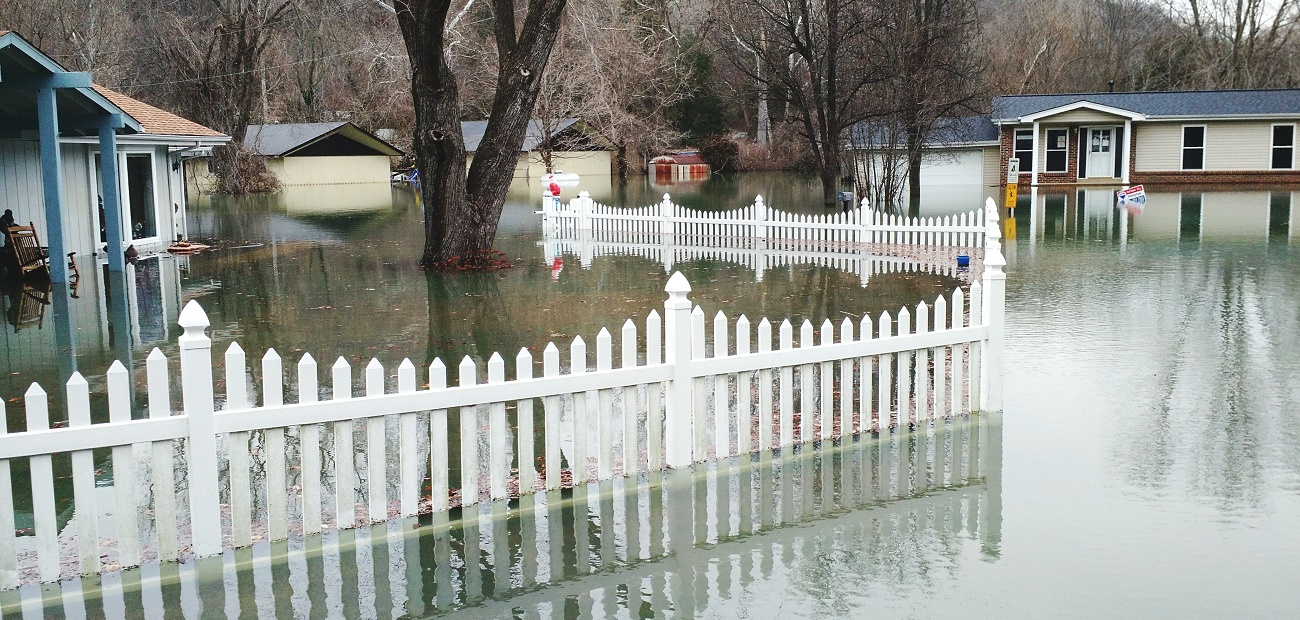 Fence In Water Amidst Houses During Flood