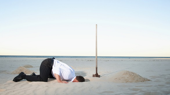 businessman burying head in sand