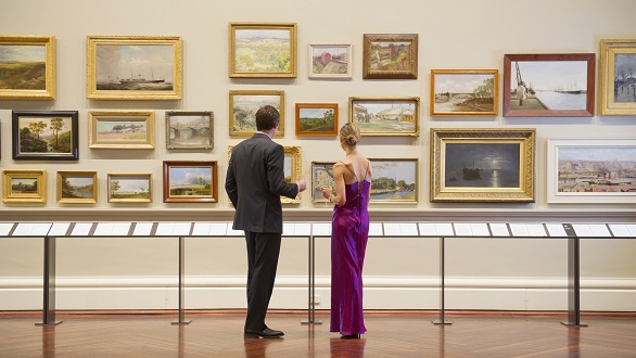 couple in evening wear admiring art in museum