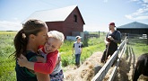 Affectionate mother holding and kissing daughter on sunny farm