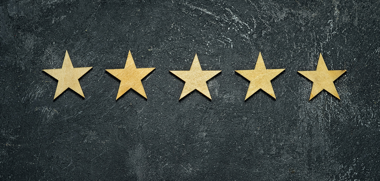 Five stars in a row on a black rustic cement board