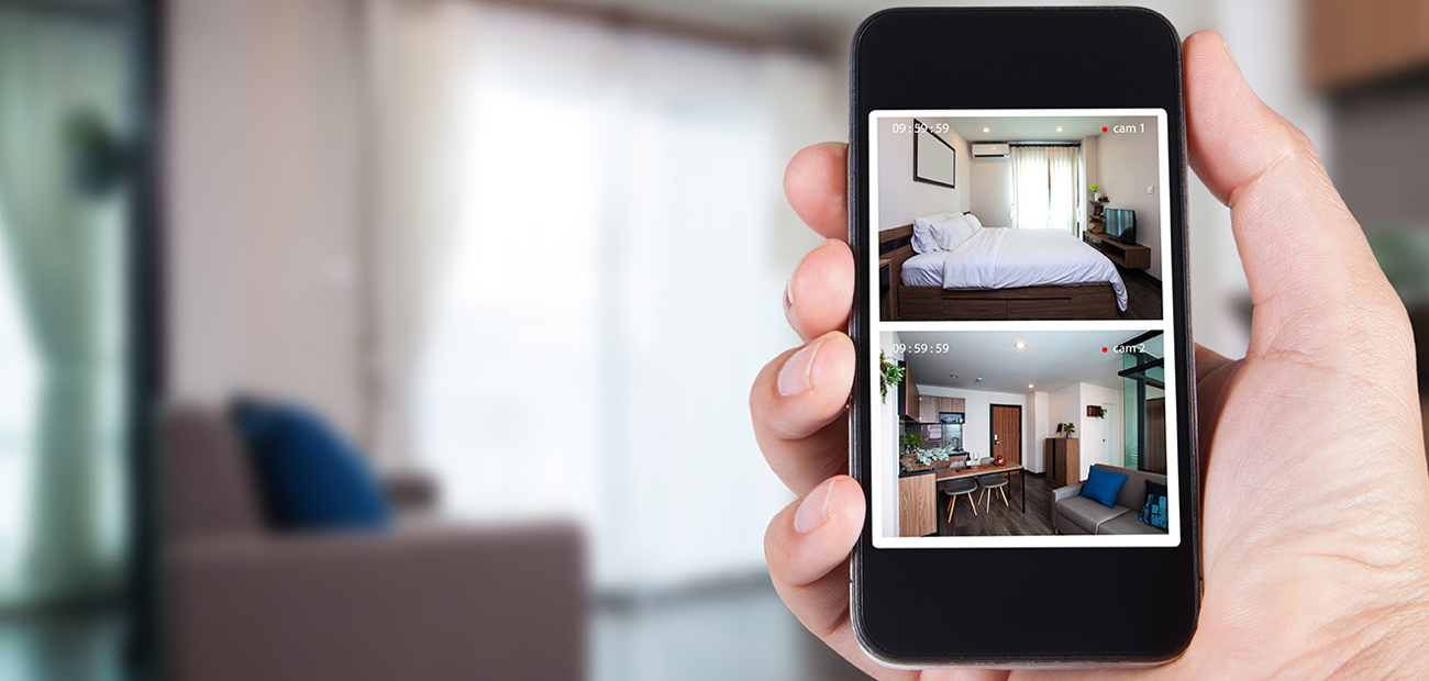Hand holding smartphone view looking in house on blurred house background with Home security CCTV system concept.