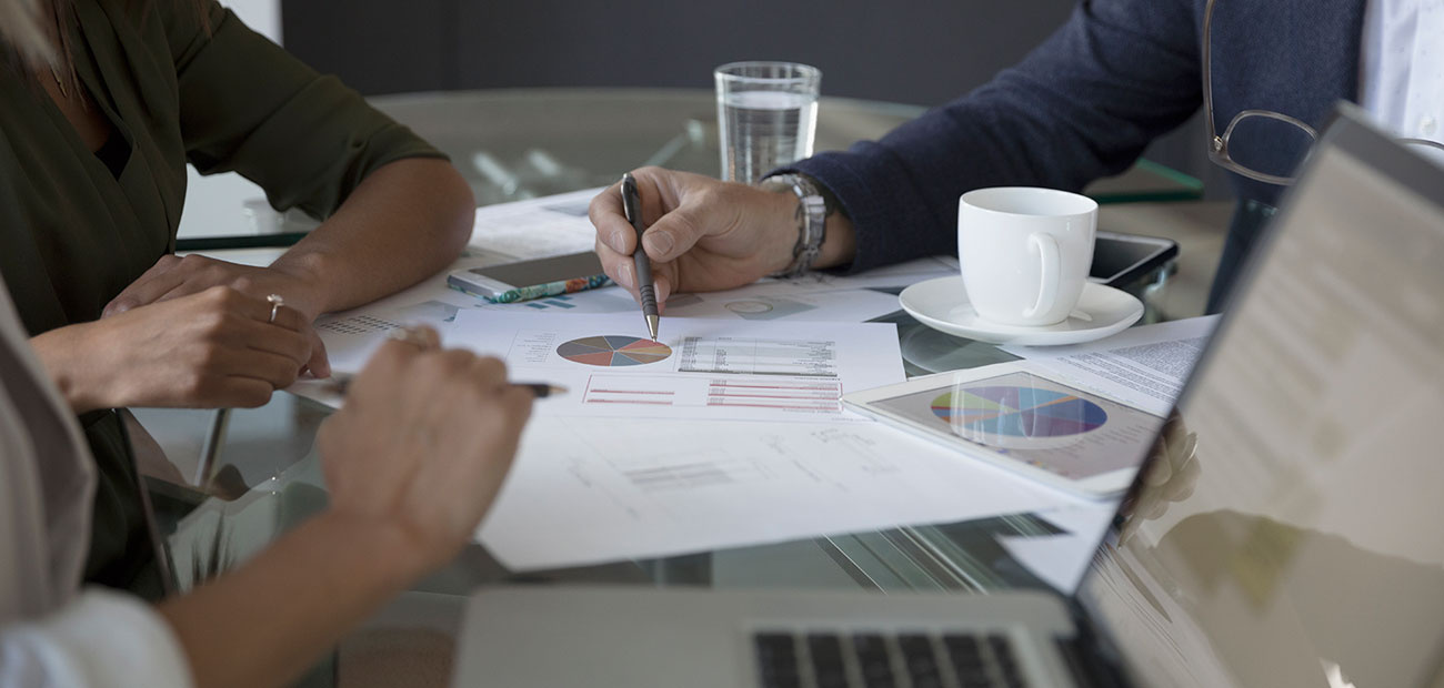 Business people reviewing financial data paperwork in conference room meeting