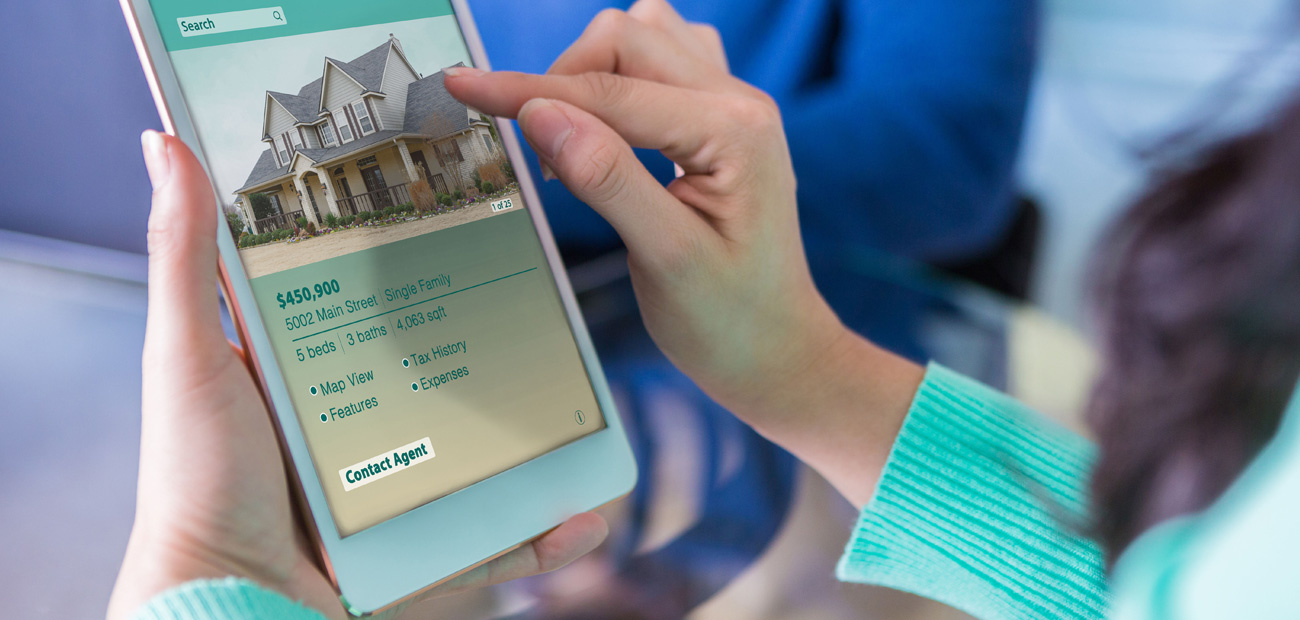 woman looking at home listing on tablet