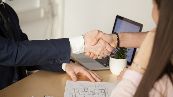 Close-up of two people shaking hands to close a deal