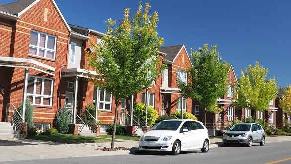 Row of attached brick homes with two cars in front