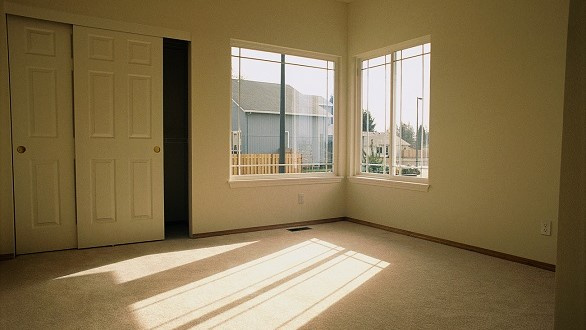 Sunlit, empty room with partially open closet door