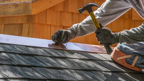 Person working on a roof with black shingles