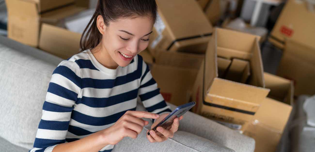 woman texting on cell phone, surrounded by moving boxes