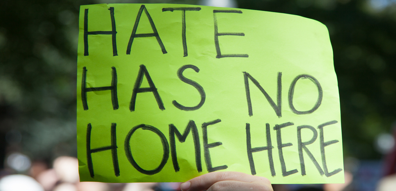 """hate has no home here"" protest sign"