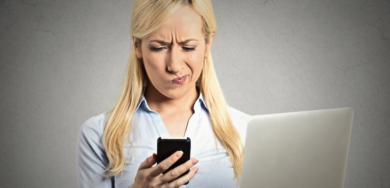 Displeased woman reading text message on phone