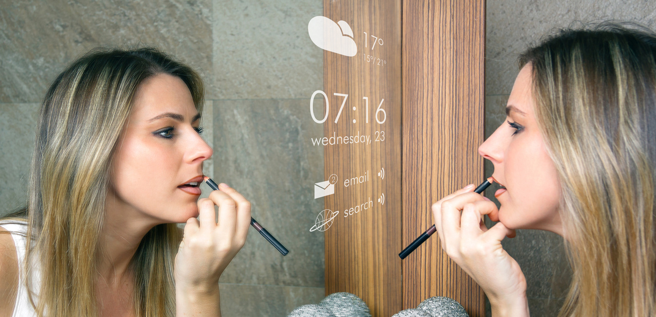 woman applying makeup by smart mirror