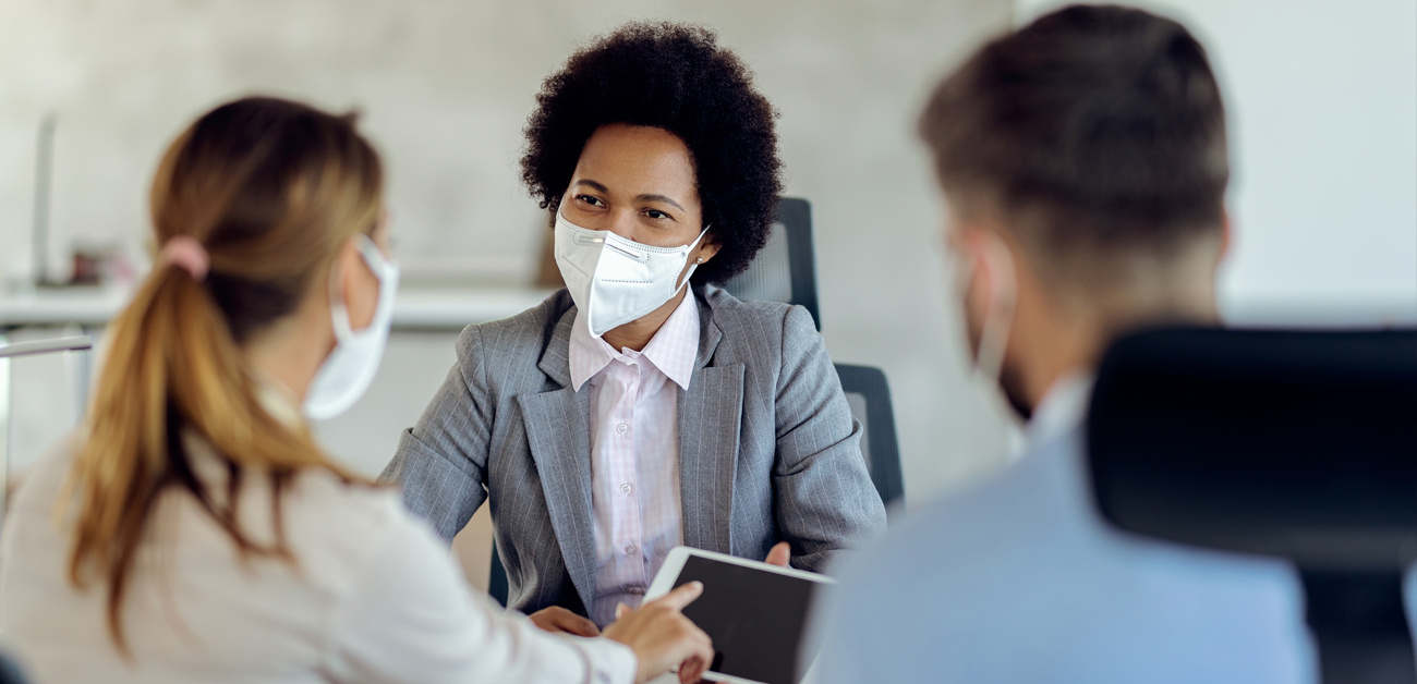 agent meeting with coworker or clients, all wear masks