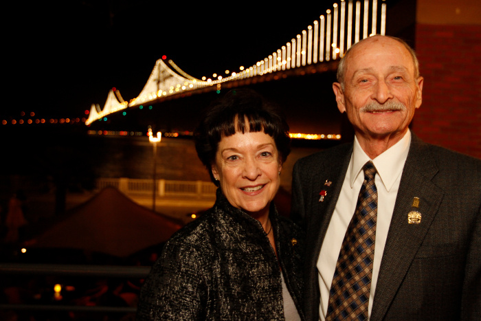 A photo of Walt McDonald and friend Sharon Bowler near San Francisco's Bay Bridge, lit up at nighttime in 2013.